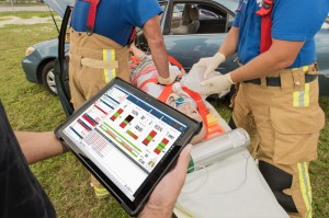 Trauma HAL patient simulator strapped to stretcher next to vehicle collision while two paramedics perform an assessment