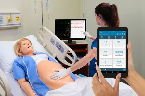 A learner feels the belly of a NOELLE simulator and reads a virtual monitor; a handheld OMNI2 controller changes the FHR